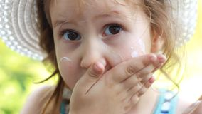 Kind schmiert seinen fase Sonnen-Creme Sonnenbrand Suncream-Creme Sonnenschutzcreme Nahaufnahmebaby stock video footage