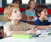 Kind in school schrijvende linkshandige Stock Foto