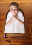 Kind am Schreibtisch mit geöffnetem Buch Stockbild