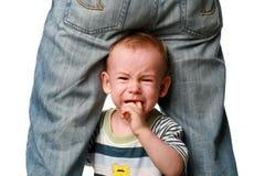 Kind schreit an den Fahrwerkbeinen des Vaters Lizenzfreies Stockfoto