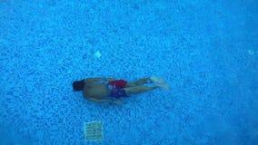 Kind schwimmt im Swimmingpool stock video footage