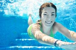 Kind schwimmt im Unterwasser-, glücklichen aktiven Jugendlichen des Swimmingpools, den Mädchen taucht und hat Spaß unter Wasser,  Stockbild