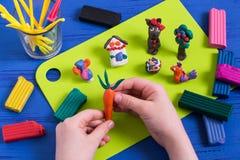 Kind sculpts Karotte vom Plasticine Stockfoto