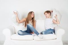 Kind-sedyat auf dem Couch- und Kissenkämpfen Stockfotos