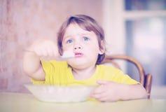 Kind selbst isst mit Löffel Stockbild