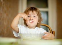 Kind selbst isst von der Platte mit Löffel Stockbilder