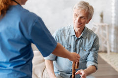 Kind senior man thanking the nurse for assistance. Help me stand up. Handsome tired elderly gentleman sitting on bed and asking the medical worker bringing him royalty free stock photography