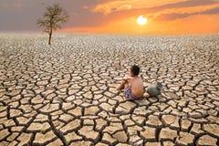 Kind sitzen auf gebrochener Erde Lizenzfreie Stockfotografie