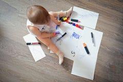 Kind sitzt auf dem Boden und zeichnet mit Bleistiften und Markierungen Lizenzfreies Stockfoto