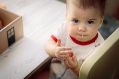 Kind sitzt auf einem Stuhl am Tisch und isst Plätzchen stockbild