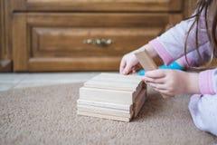 Kind sitzt auf Teppich und Spiel durch hölzerne Spielwaren, Entwicklung, Nahaufnahme Lizenzfreie Stockfotografie