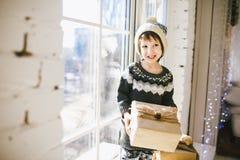 Kind sitzt am Fenster an einem sonnigen Weihnachtstag und macht mit Geschenken in den Kästen aus, die im Papier eingewickelt werd stockbild