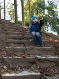 Kind sitzt mit offenem Mund am Hintergrund von Bäumen Stockbilder