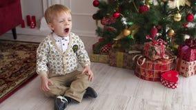 Kind sitzt nahe dem Weihnachtsbaum und gähnt stock footage