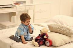 Kind in slaapkamer met stiltegebaar Tijd aan slaapconcept De jongen met gelukkig gezicht zet favoriet stuk speelgoed op bed, tijd royalty-vrije stock foto