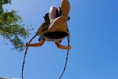 Kind slingerende hoogte op een speelplaatsschommeling Stock Afbeelding