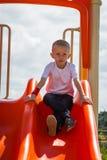 Kind in speelplaatsjongen het spelen op dia Stock Fotografie