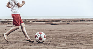 Kind speelvoetbal op het strand stock foto's
