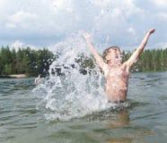 Kind spritzt vom Wasser um ein Schwimmertauchen in das Wasser Kind aufgeregt über Schwimmen Stockfotografie