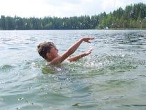 Kind spritzt vom Wasser um einen Schwimmer, das Kind, das über Schwimmen aufgeregt wird Das Konzept einer glücklichen Kindheit Stockfoto