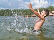 Kind spritzt vom Wasser um einen Schwimmer, das Kind, das über Schwimmen aufgeregt wird Das Konzept einer glücklichen Kindheit Stockfotos