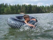 Kind spritzt vom Wasser um einen Schwimmer, das Kind, das über Schwimmen aufgeregt wird Das Konzept einer glücklichen Kindheit Stockfotografie