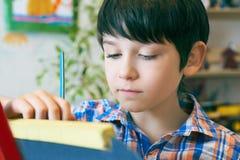 Kind-standingnext zum Gestell Kinderjunge lernen Farbe durch Bürste in der Klassenschule Kindergarteninnenraum auf Hintergrund Ju Stockfoto