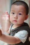Kind stehen Fenster bereit Stockbilder