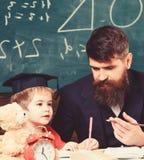 Kind studiert mit dem Lehrer und hört mit Aufmerksamkeit Volksschulbildungskonzept Lehrer und Schüler in der Doktorhut stockbilder