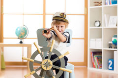 Kind täuschen vor, Seemann zu sein Scherzen Sie den Jungen, der durch das Spionsglas schaut, das zu Hause spielt stockbild