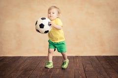 Kind täuscht vor, ein Fußballspieler zu sein Lizenzfreies Stockbild