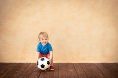 Kind täuscht vor, ein Fußballspieler zu sein Lizenzfreie Stockfotos