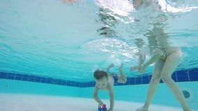 Kind taucht unter Wasser unter der Steuerung seiner Mutter stock video