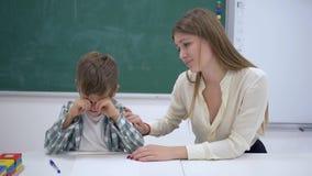 Kind teacher calms crying scholar boy during extracurricular activities at desk near blackboard in classroom of school. Kind teacher calms crying scholar boy stock video footage