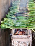 Kind of Thai sweetmeat. Thai sweetmeat made of flour with coconut and sugar wrapped in leaves next to the wall Stock Images