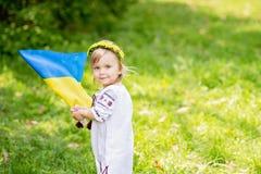 Kind tr?gt flatterndes Blau und gelbe Flagge von Ukraine auf dem Gebiet Ukraine-` s Unabh?ngigkeitstag Feierlicher Hintergrund mi lizenzfreies stockfoto