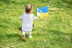 Kind tr?gt flatterndes Blau und gelbe Flagge von Ukraine auf dem Gebiet Ukraine-` s Unabh?ngigkeitstag Feierlicher Hintergrund mi lizenzfreie stockfotos
