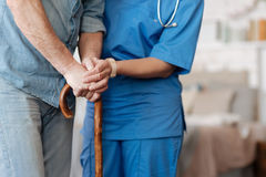 Kind trained nurse helping feeble gentleman walking. Be careful. Active productive admirable women holding her patient by the hand making sure he standing firmly stock photo