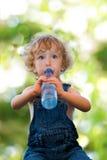 Kind in Trinkwasser der Denimklage Stockbild