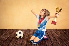 Kind täuscht vor, ein Fußballspieler zu sein Stockbild