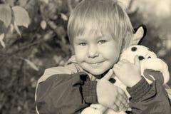 Kind umfaßt ein Spielzeug Stockfoto