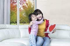 Kind umfasst ihre Mutter auf Sofa Lizenzfreie Stockbilder