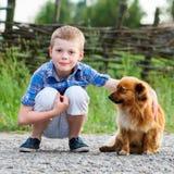 Kind umfasst liebevoll seinen Schoßhund Beste Freunde outdoor lizenzfreie stockbilder
