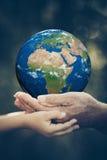 Kind und das ältere Halten bedecken Planeten in den Händen mit Erde Stockfotos