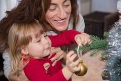 Kind und Frau, die Ball in Weihnachtsbaum legen Stockbilder