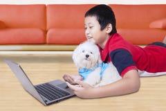 Kind und Hund unter Verwendung des Laptops zu Hause Stockbilder