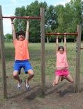 Kind und kleines Mädchen, die von den Pfosten hängen, um Gymnastik zu tun Stockbild