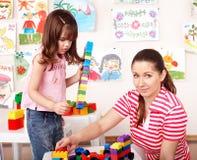 Kind und Lehrer mit Aufbau lego. Lizenzfreie Stockfotos