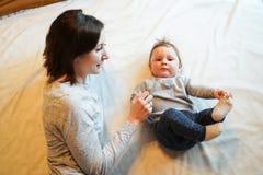 Kind und Mutter auf Bett Mutter und Baby, die im sonnigen Schlafzimmer spielen Elternteil und Kleinkind, die sich zu Hause entspa stockbild