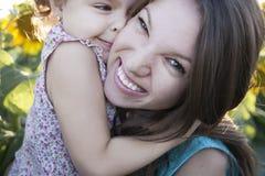 Kind und Mutter auf Sonnenblumen Lizenzfreie Stockfotos